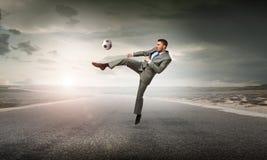Uomo d'affari che dà dei calci alla palla Immagine Stock