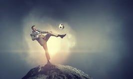 Uomo d'affari che dà dei calci alla palla Fotografia Stock Libera da Diritti