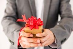 Uomo d'affari che dà un regalo con il nastro rosso Fotografie Stock