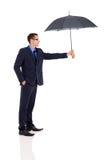 Uomo d'affari che dà ombrello Immagini Stock