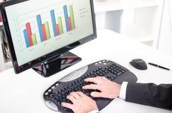 Uomo d'affari che digita su una tastiera di calcolatore Immagini Stock