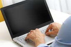 Uomo d'affari che digita sul computer portatile fotografia stock