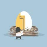 Uomo d'affari che dipinge colore dorato sull'uovo Immagini Stock Libere da Diritti