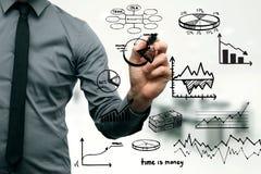 Uomo d'affari che disegna i grafici e i chartss differenti Immagine Stock