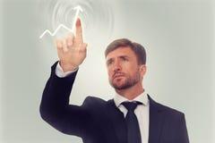 Uomo d'affari che disegna una freccia sullo schermo Fotografia Stock