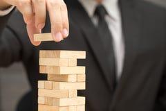 Uomo d'affari che dispone blocco di legno su una torre Rischio e strategia i Immagini Stock