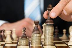Uomo d'affari che dispone i pezzi degli scacchi sulle monete impilate Immagine Stock Libera da Diritti