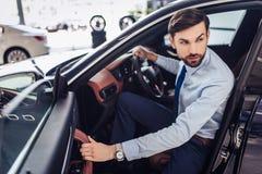 Uomo d'affari che distoglie lo sguardo mentre sedendosi in automobile immagini stock libere da diritti