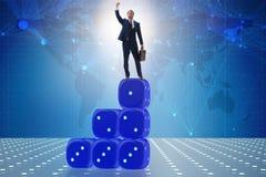 Uomo d'affari che equilibra sopra la pila dei dadi nel concep di incertezza Fotografie Stock Libere da Diritti