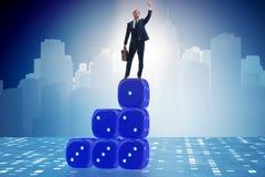Uomo d'affari che equilibra sopra la pila dei dadi nel concep di incertezza Fotografie Stock