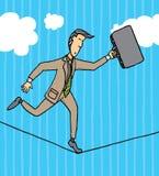 Uomo d'affari che equilibra su una corda Immagini Stock
