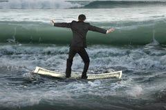 Uomo d'affari che equilibra sul crogiolo di soldi che galleggia nell'oceano con le onde Immagini Stock Libere da Diritti