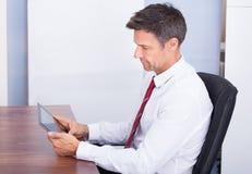 Uomo d'affari che esamina compressa digitale Immagini Stock
