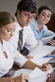 Uomo d'affari che esamina i documenti nella riunione Fotografia Stock