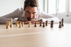 Uomo d'affari che esamina i pezzi degli scacchi in bianco e nero sull'ufficio de immagini stock libere da diritti