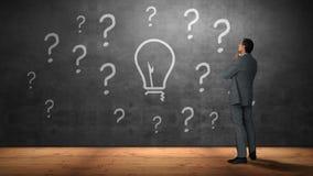 Uomo d'affari che esamina i punti interrogativi e la lampadina stock footage