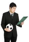 Uomo d'affari che esamina il cuscinetto dell'archivio e che tiene pallone da calcio Immagine Stock Libera da Diritti