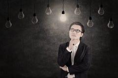 Uomo d'affari che esamina lampadina accesa Immagini Stock Libere da Diritti