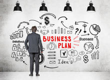 Uomo d'affari che esamina le icone del business plan Immagine Stock
