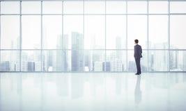 Uomo d'affari che esamina megalopoli attraverso la finestra Immagine Stock