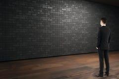 Uomo d'affari che esamina muro di mattoni vuoto Immagini Stock Libere da Diritti