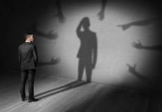 Uomo d'affari che esamina ombra in cui molte mani raggiungono per lui che forza la gru a benna la sua testa Immagine Stock Libera da Diritti