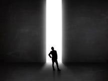 Uomo d'affari che esamina parete con l'apertura leggera del tunnel Fotografie Stock Libere da Diritti