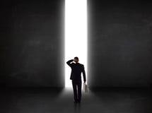 Uomo d'affari che esamina parete con l'apertura leggera del tunnel Immagini Stock