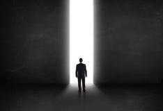 Uomo d'affari che esamina parete con l'apertura leggera del tunnel Fotografia Stock Libera da Diritti