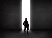 Uomo d'affari che esamina parete con l'apertura leggera del tunnel Immagini Stock Libere da Diritti