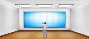 Uomo d'affari che esamina plasma in bianco TV Fotografia Stock Libera da Diritti
