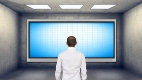 Uomo d'affari che esamina plasma in bianco TV Immagine Stock Libera da Diritti