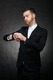Uomo d'affari che esamina preoccupato l'orologio Fotografia Stock