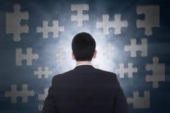 Uomo d'affari che esamina puzzle Fotografia Stock Libera da Diritti