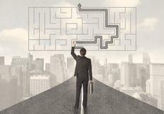 Uomo d'affari che esamina strada con labirinto e la soluzione Immagine Stock Libera da Diritti