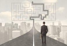 Uomo d'affari che esamina strada con labirinto e la soluzione Immagini Stock Libere da Diritti