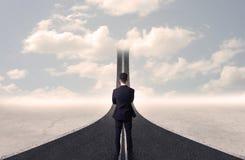 Uomo d'affari che esamina strada 3d che va su nel cielo Immagini Stock