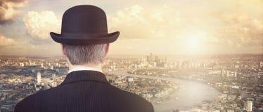 Uomo d'affari che esamina tramonto sopra l'orizzonte della città immagine stock libera da diritti