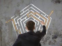 Uomo d'affari che esamina un labirinto Immagine Stock Libera da Diritti