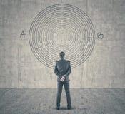 Uomo d'affari che esamina un labirinto sulla parete Fotografia Stock Libera da Diritti