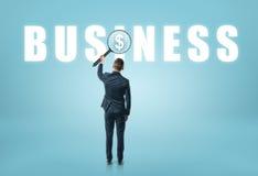 Uomo d'affari che esaminano & x27; business& x27; parola con la lente ed il simbolo di dollaro vedere Fotografia Stock