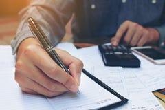 Uomo d'affari che fa le finanze con per mezzo del calcolatore e la scrittura nessuna Immagine Stock Libera da Diritti