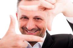Uomo d'affari che fa struttura gesture e che esamina macchina fotografica immagine stock libera da diritti