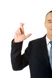 Uomo d'affari che fa un desiderio con le dita attraversate Fotografia Stock Libera da Diritti