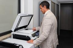 Uomo d'affari che fa una fotocopia Immagini Stock
