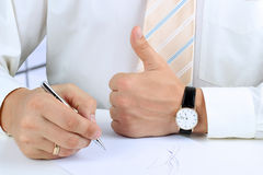 Uomo d'affari che firma un documento e che mostra segno GIUSTO con il suo Thu Immagini Stock