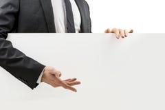 Uomo d'affari che gesturing ad un bordo bianco in bianco Fotografia Stock