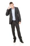 Uomo d'affari che gesturing con il dito contro il tempio Fotografie Stock Libere da Diritti