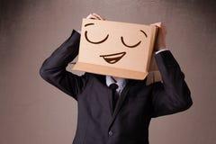 Uomo d'affari che gesturing con una scatola di cartone sulla sua testa con smil Fotografia Stock