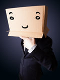 Uomo d'affari che gesturing con una scatola di cartone sulla sua testa con smil Fotografia Stock Libera da Diritti